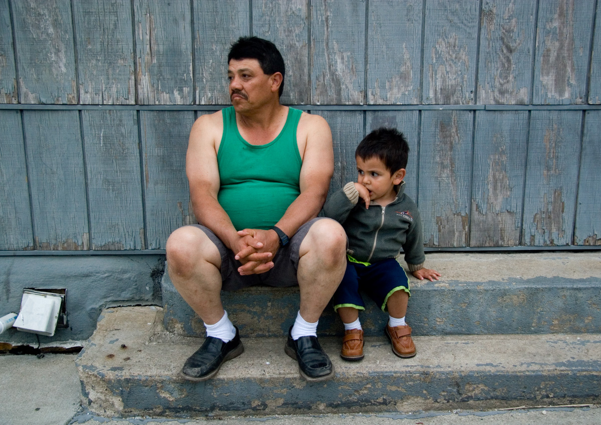 "Pedro rests on a stoop with his grandson during a walk through town in the early evening.  Sean calls Pedro ""Papa"" because he does not know his real father, who was deported during the raid."