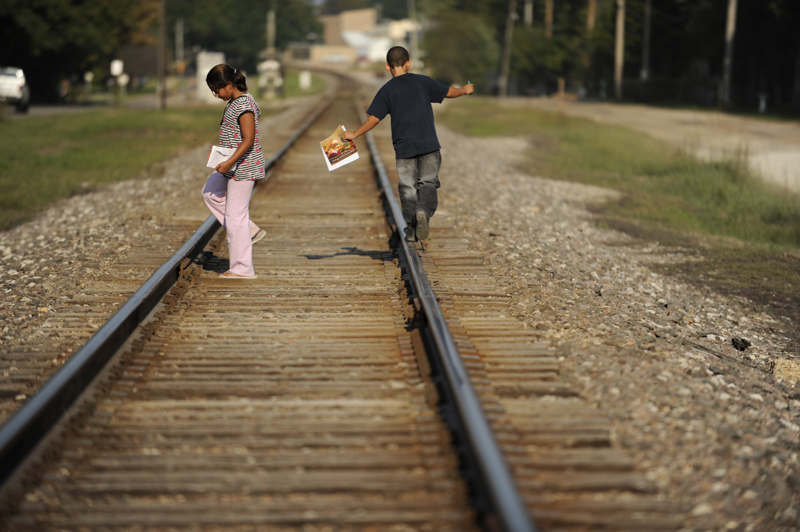 Walking along the railroad tracks that run through town, Sierra and Micheal wander to various neighbor's homes while selling candles as part of a school fundraiser.